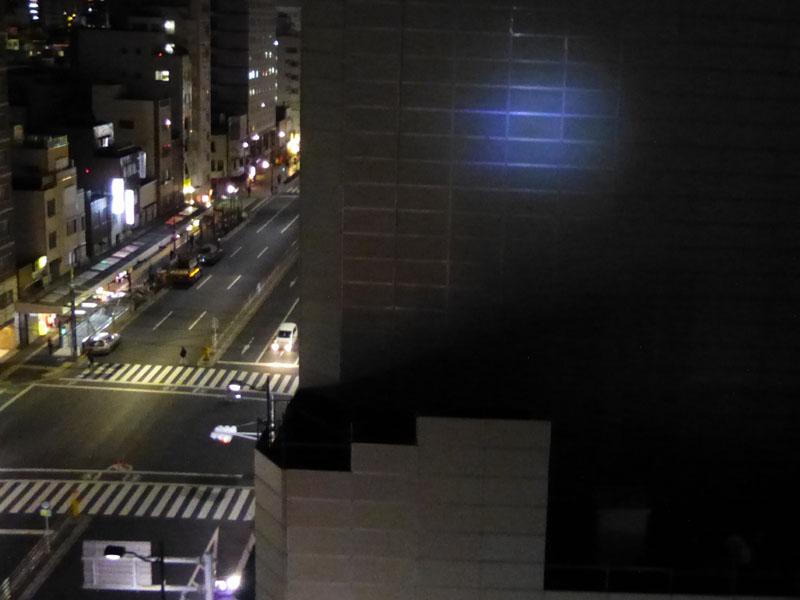 50mほど離れたビルの外壁まで明かりが届く。右上の明るい部分が照射した光