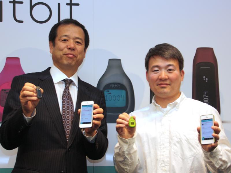 製品を手に、左からソフトバンクBBの溝口泰雄 取締役常務執行役員と、Fitbitのジェームズ・パークCEO