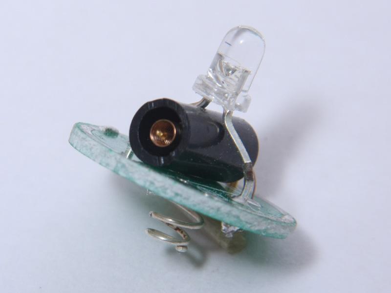 中央黒い筒の中心に銅線が1本突き出ていて、それを囲むようにスプリング状の銅線が備えられている。セーフティーライトがゆれると、スプリング状の銅線が揺れて中心の銅線に触れ、LEDが光るという仕組み