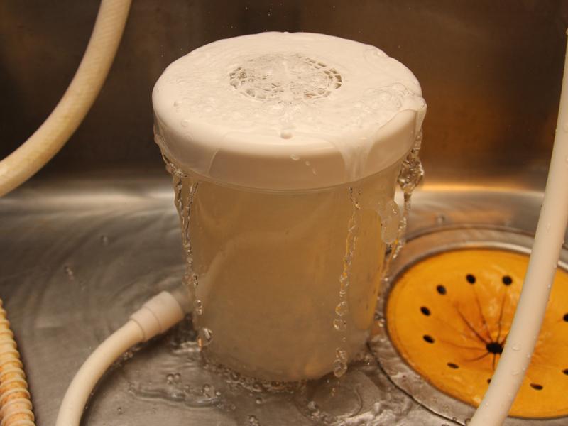 フタをして水を流すと、内部の米が回転。その後、研ぎ汁がフタから溢れる