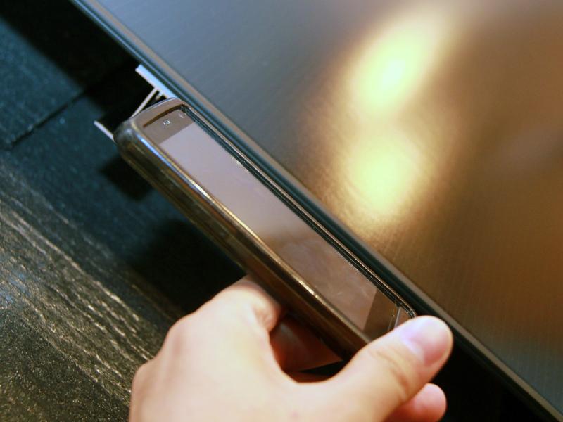 ソラシス・ネオとスマートフォンと比べてみた。写真のスマートフォンは保護ケースを付けているため、ソラシス・ネオの方が薄かった