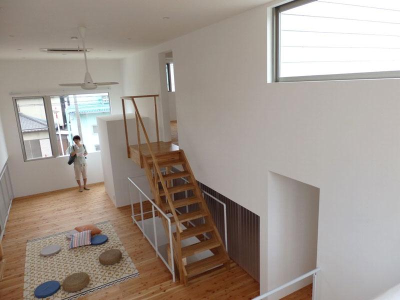 3階踊り場から2階の共有スペースを眺めたところ。階段の奥にある白い箱状のスペースはトイレだ