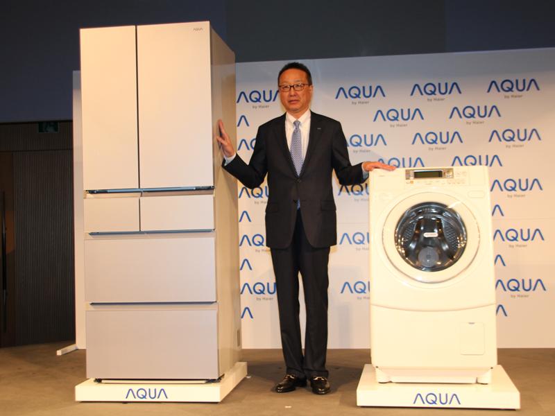 中川喜之代表執行取締役社長と11月下旬発売の新製品。左から冷蔵庫、ドラム式洗濯乾燥機
