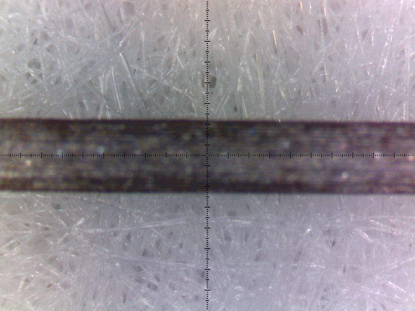 HEPAフィルターの顕微鏡写真(230倍)。中央に見えるのは0.3mmのシャープペンの芯。目がどれだけ細かいか分かる