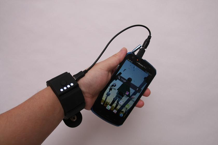 腕につけると、厳ついGショック(腕時計)をつけた感覚だ。充電しながらスマートフォンを使うとこんな感じ。ケーブルがちょっと、ほんのちょっとだけ短い……
