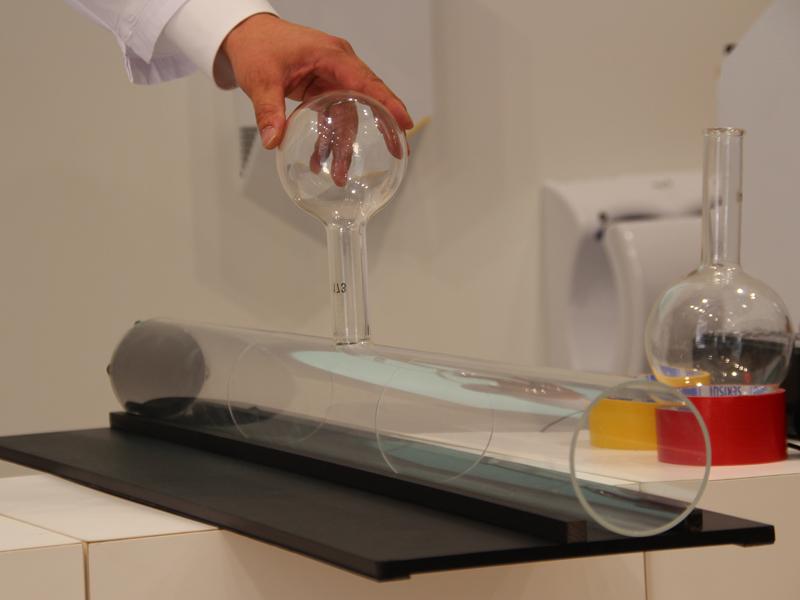 ヘルムホルツ式空洞の原理をわかりやすく説明。スピーカーを付けたガラスの筒の途中にビーカーを付けると、音が小さくなった