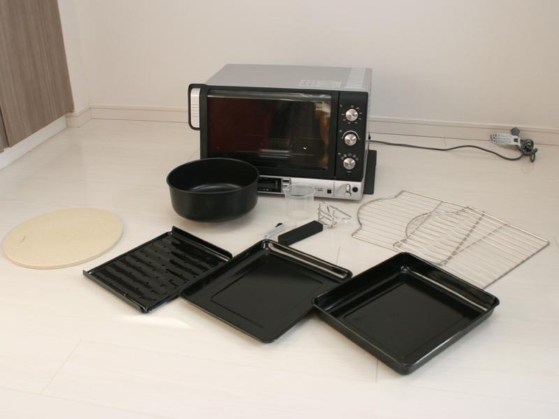 トレイ2枚、ワイヤーラック2枚、肉を焼くときに使うオイルプレート、ピザを焼く時に使う、ピザストーン、トレイを取り出す時に使うグリップ、パンボウル、計量カップ、計量スプーンが付属する