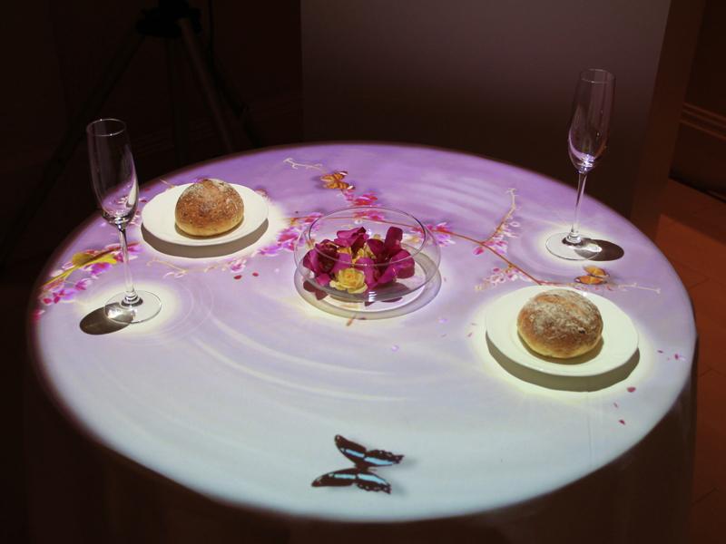 レストランでは、料理にはおいしく見せる照明光を、グラスにはきらめきが増す光を投影できるほか、テーブルにメニューなどの文字情報を投影することも可能
