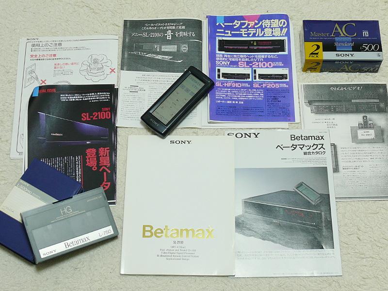 リモコンもタッチパネル式(中央)。金文字のβマックスが光る取扱説明書。当時のカタログと共に、発売前のレビュー記事のコピーがまだ手元にある。ライブラリ以外に新品のテープもまだ持っている