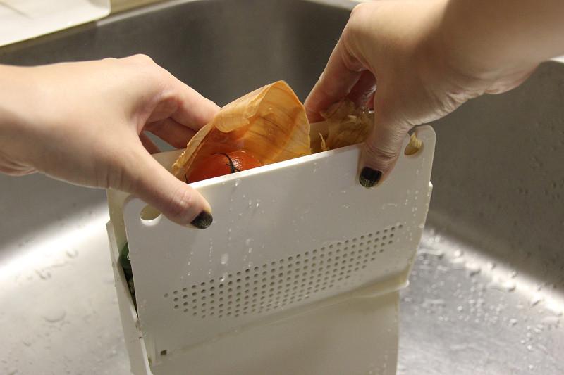 水切り器の上部を掴んでゆっくり挟む。水が絞れた