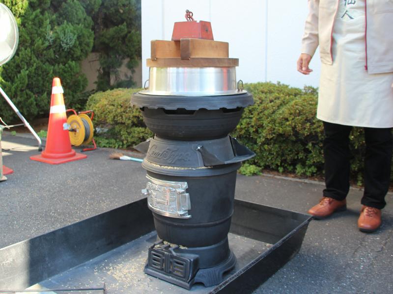 羽釜には2升米を入れ、洗米してぬか釜にセット。木蓋の上にはお米が吹いても持ち上がらないように、重石を載せる