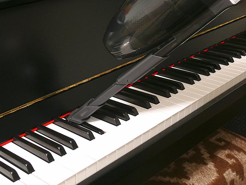 ハンディクリーナーにして、ピアノの鍵盤上を掃除している様子。ブラシが柔らかい