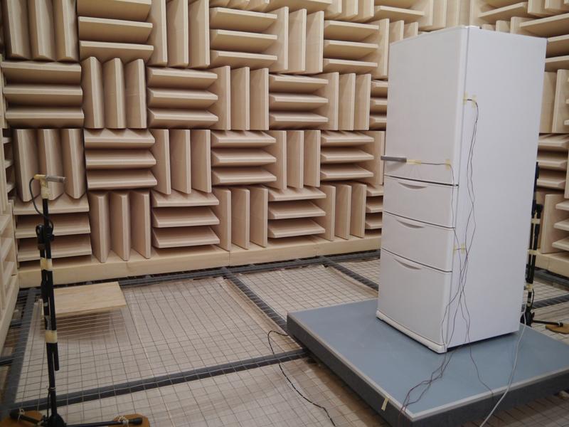 無響音室では、冷蔵庫の前方と後方からマイクを使って稼働音を検査