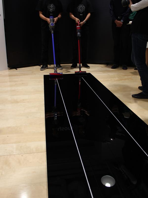 アクリル板の溝に重曹を撒き、それを吸引するというデモンストレーション。左がダイソン、右が東芝