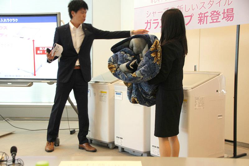 身長150cm台の女性が、毛布を「ES-GX850」の洗濯槽に入れる実演