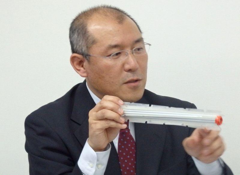 新たに搭載されたカーペット用の新型ブレードブラシを持って説明する製品担当の堀田正幸氏
