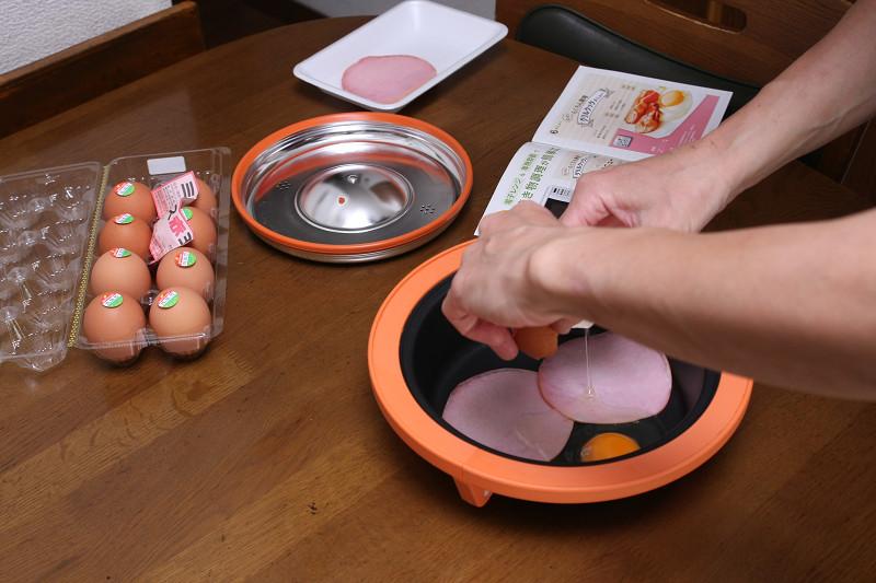 専用フライパンにハムを敷き卵を落として「ハムエッグ」ボタンを押すだけ。あとは3分まつだけ。オレンジの部分は樹脂製で熱くない