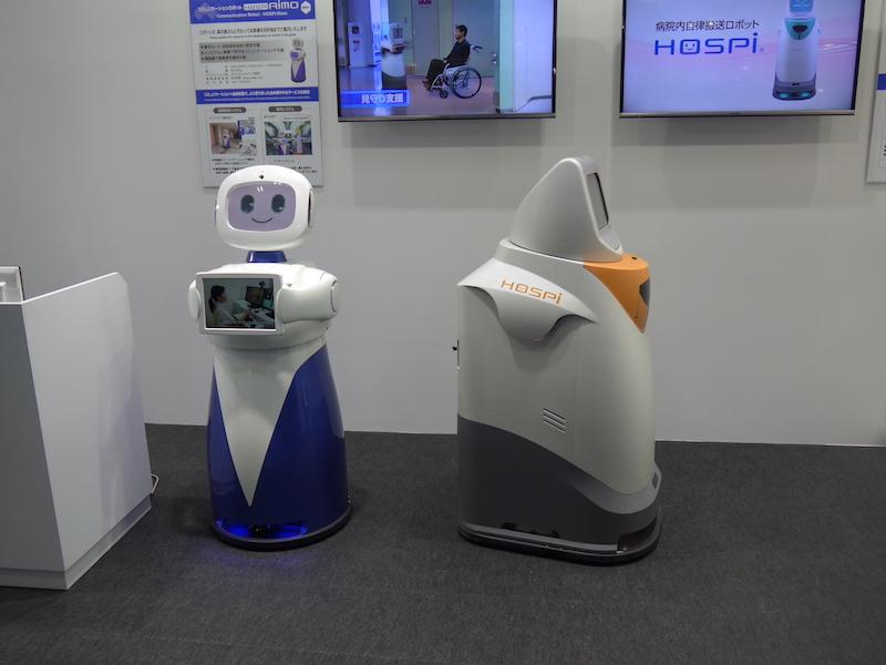 病院内での薬剤搬送などに使われているパナソニックの「HOSPi」(写真右)と、会話や案内機能を追加するなどが検討されている開発中の「HOSPi-Rimo」