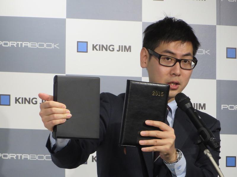 キングジム 商品開発部の冨田正浩氏。右手に持っているのがポータブックで、左手に持つのがA5サイズの手帳