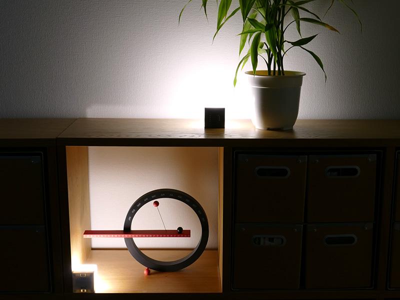 棚に2個のエネヴュー キューブを置いてアクセントライトとして活用。光源を壁に向ければ、壁からの反射光が部屋に優しく拡散する