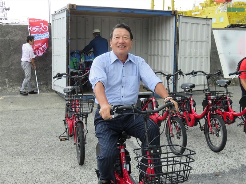 コンテナから降ろされた自転車にまたがるNTTドコモ 顧問の山田隆持氏