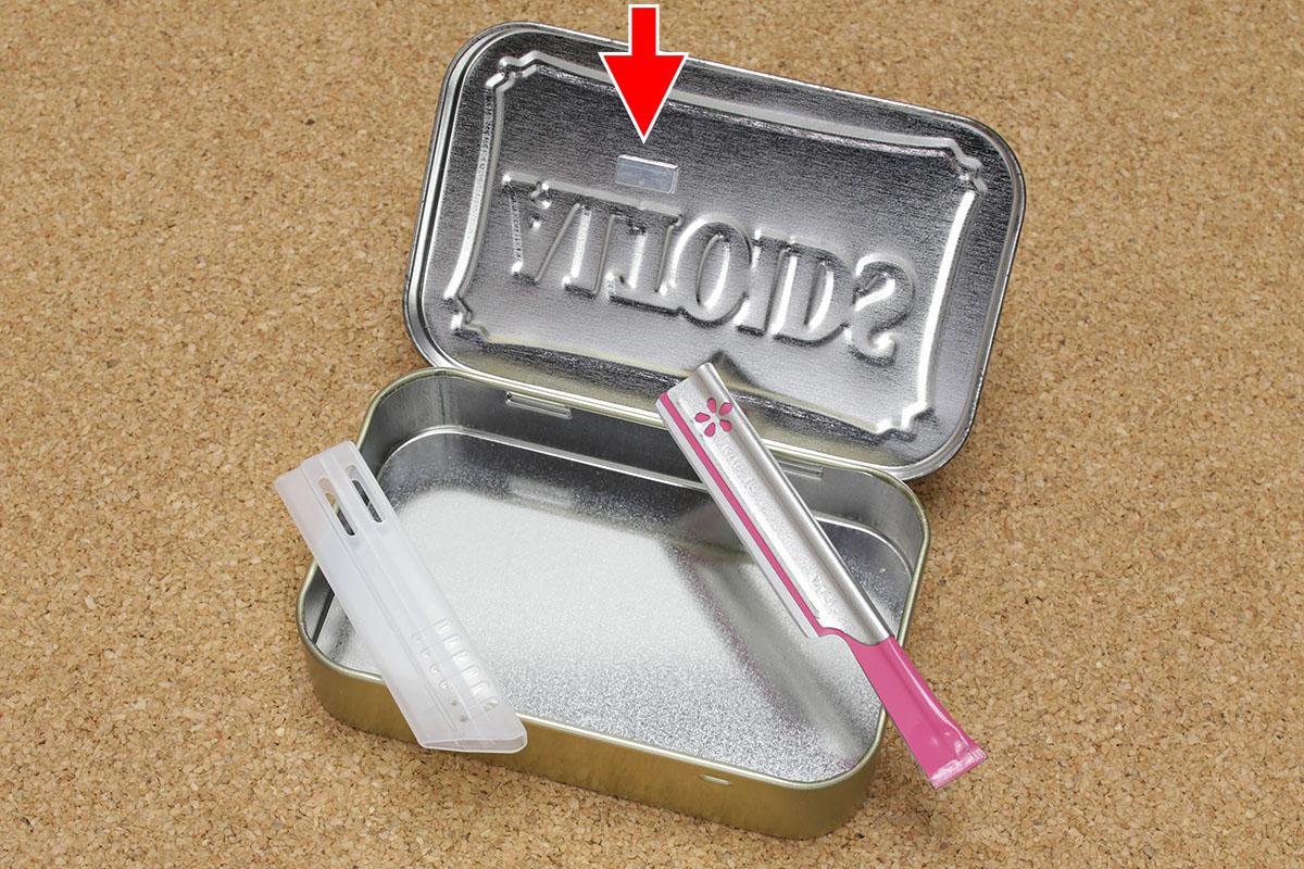 """ALTOIDS缶に「Waterproof Straw Containers」を入れた様子。缶毎に「非常用」「おやつ」「着火道具」などと分けたりするのも愉快です。ちなみに缶蓋の裏には、短く切断したカミソリをネオジム磁石(赤矢印)で吸着させています。このカミソリはKAIの「長柄カミソリ ビューティーM」(<a href=""""http://www.kai-group.com/store/products/detail/3103"""" class=""""n"""" target=""""_blank"""">公式ページ</a>)で、使い捨てですが安価で切れ味が鋭く刃先カバー付きで、ツイデに柄を短くカットしやすかったりします。なので、「Waterproof Straw Containers」の開封用としてなかなか便利!"""