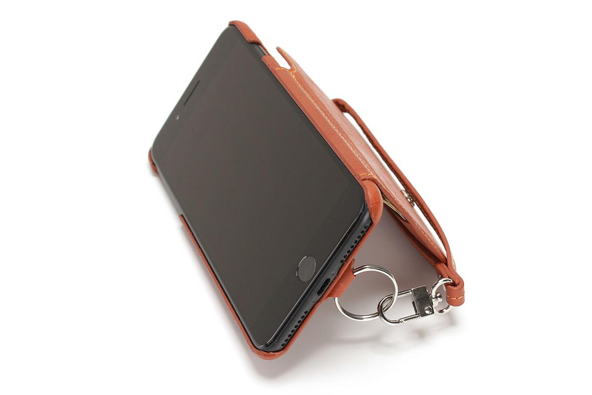 iPhone 7 Plus用の「RAKUNI」の場合、付属ストラップを写真のように使えば非常に安定的に横置きできます。金具の向きを調節しつつリングに引っ掛けるなどすれば、安定を保ちつつ角度も変えられました。
