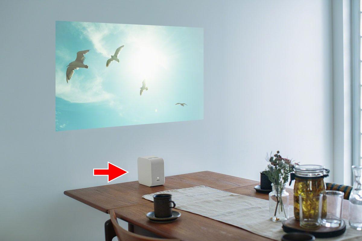 赤矢印がプロジェクター本体。壁際ギリギリに置いて壁に投影したり、机上などに置いて机面に投影したりできます。22インチから80インチの映像を映し出せます。
