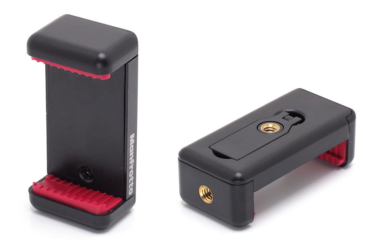 """ちなみに、樹脂製の「スマートフォン用三脚アダプター」(<a href=""""https://www.manfrotto.jp/universal-smartphone-clamp-with-thread-connections"""" class=""""n"""" target=""""_blank"""">公式ページ</a>)という製品もあります。こちらはバネ式で、底面と背面に三脚ネジ穴があります。簡易的なスタンド機能も。メーカー価格は税別1500円。"""