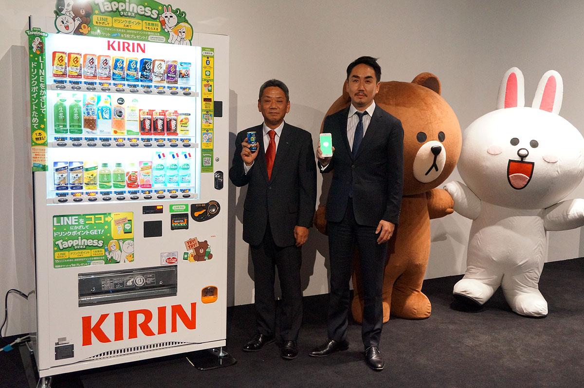 キリンの自販機と並ぶ、キリンビバレッジバリューベンダーの岩田氏とLINEの出澤氏