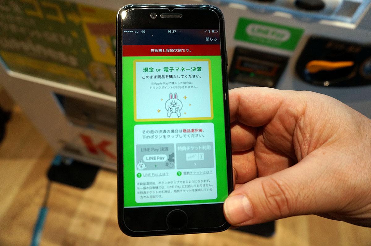 自販機で買いたい商品を選びボタンを押しつつ、画面で支払い方法を選ぶ