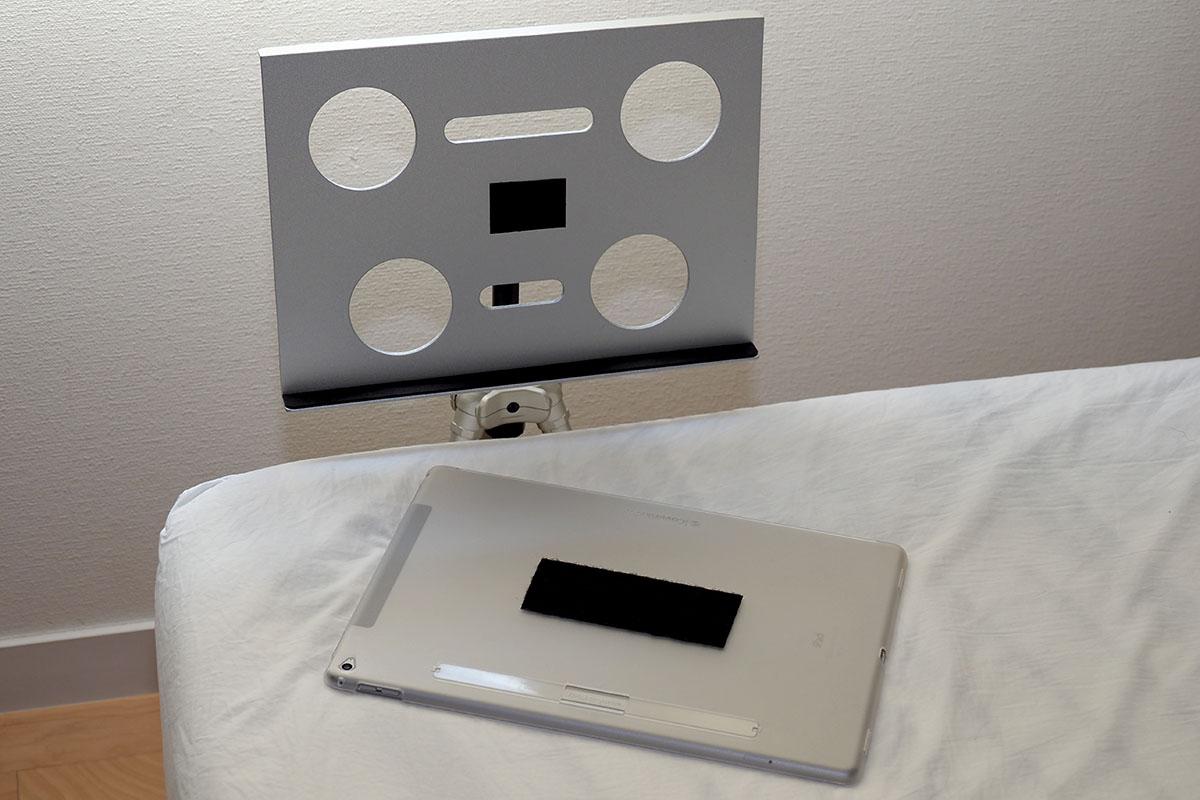 置くだけでは不安という場合、タブレットをケースに入れ、ケースと「カメラ三脚用ノートPCデスク CLHCMAL2」に面ファスナーテープ(貼り付け用粘着テープ付き)を貼り、簡易的に固定する方法もあります。ただこの方法だと、ケースの材質やテープを貼る大きさなどにより、面ファスナーテープが剥がれてしまうこともありますので注意が必要です。耐震用の粘着パッドを貼る方法も良さそうです。