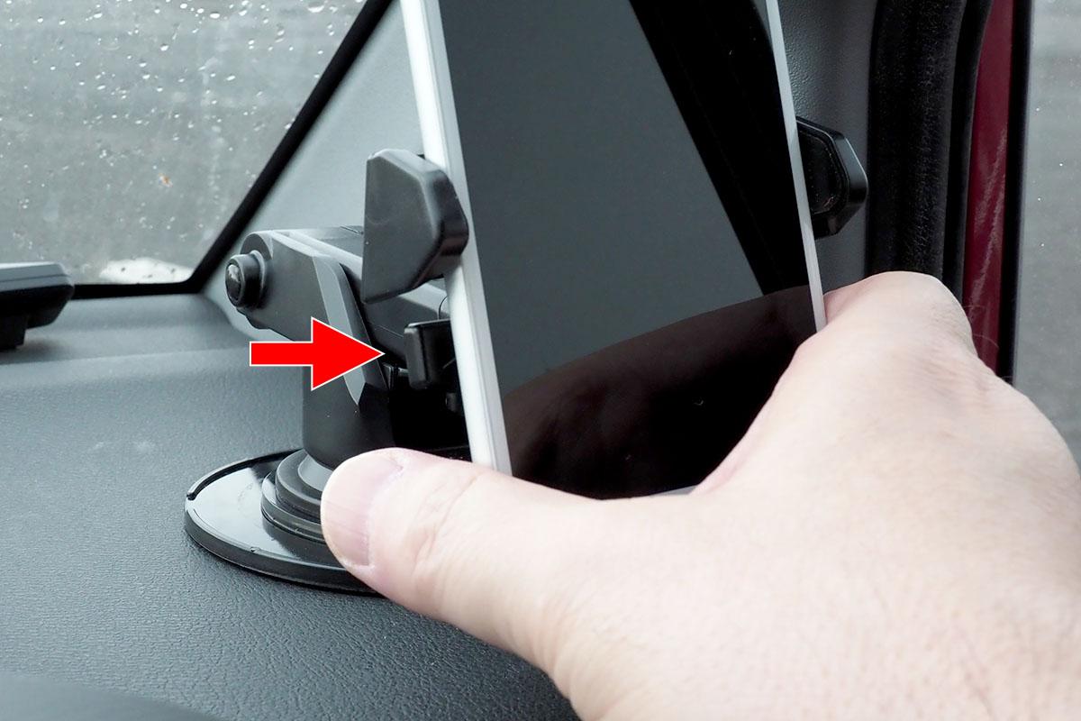 片手でホルダーから外すこともできます。赤矢印の部分を指で押すとホルダーが開きますので、そのまま端末を引き抜けばOK。その状態でホルダーが開いたまま固定されますので、再度端末をホルダーに置けば自動的に保持。脱着が片手で行える自動ホルダーというわけです。
