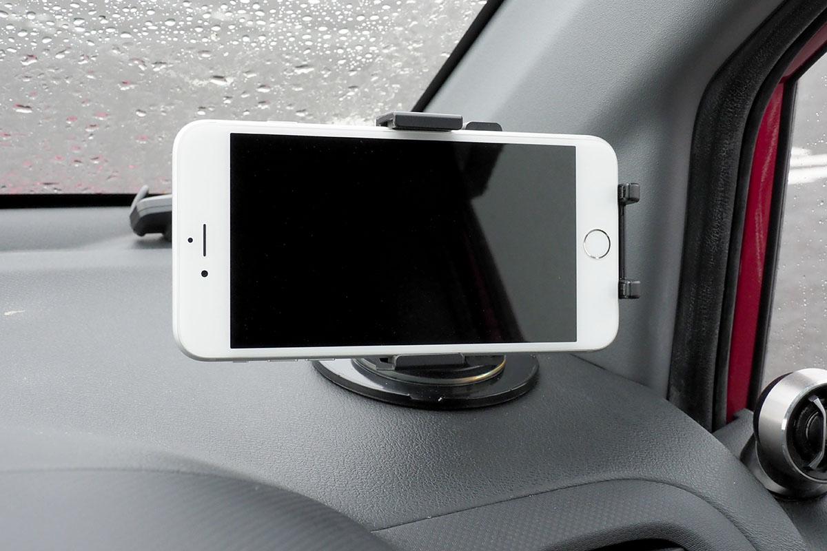 車内に設置した様子。ホルダー中央の丸いボタンが押されるようスマートフォンを置くと、自動的にホルダーが閉じて端末が固定されます。端末の向きや角度も十分な自由度をもって調節できます。