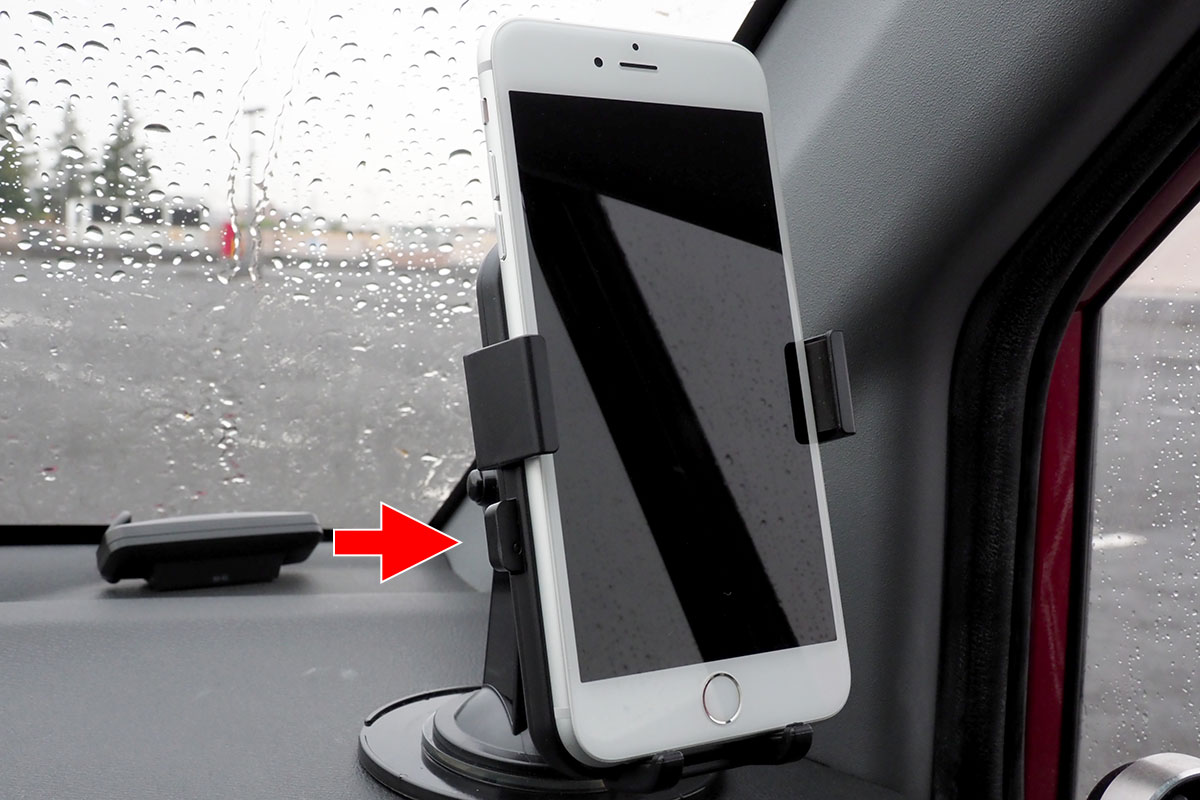 左右のボタンが押し込まれた状態で、端末を置きます。軽く置いて、画面中央をポンと押してホルダーの丸いボタンを押してもいいでしょう。ホルダーが閉じて端末が保持されると、ホルダー左右のボタンが少し飛び出します。