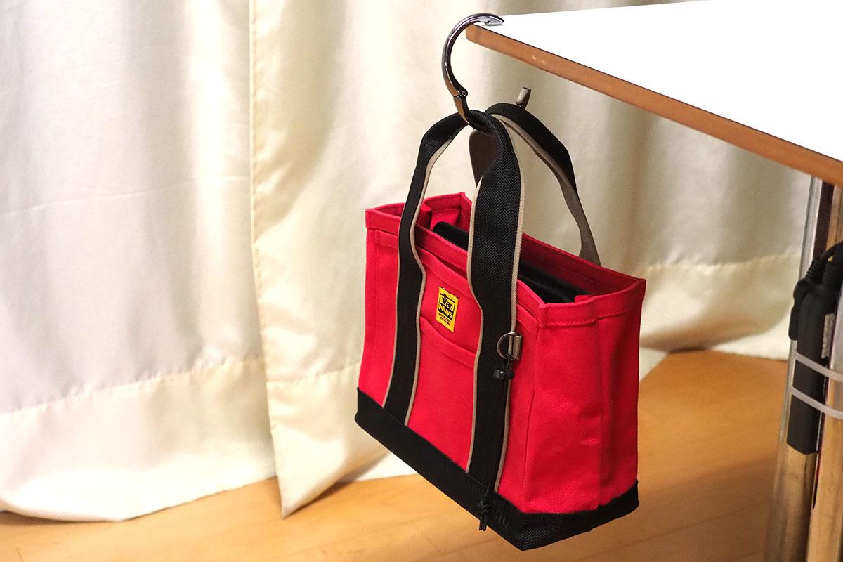 通称「バッグハンガー」として売られている「バッグを吊すための小道具」。取っ掛かりのないテーブルなどに、臨時的にバッグなどを吊しておくことができるグッズです。