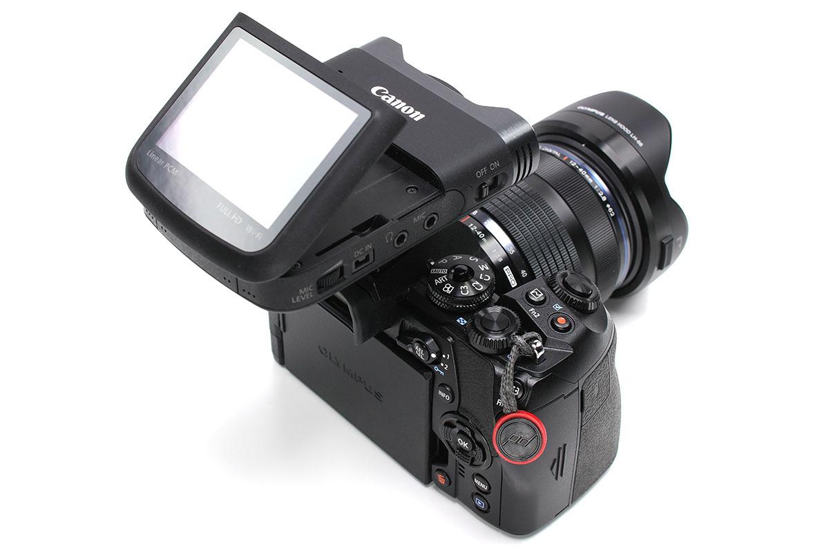 オリンパス「OM-D E-M1 Mark II」に「iVIS mini X」を装着。これで移動しつつの取材をすることがあります。この合体カメラを手に持って動画を撮り続け、必要に応じて静止画を撮影しています。
