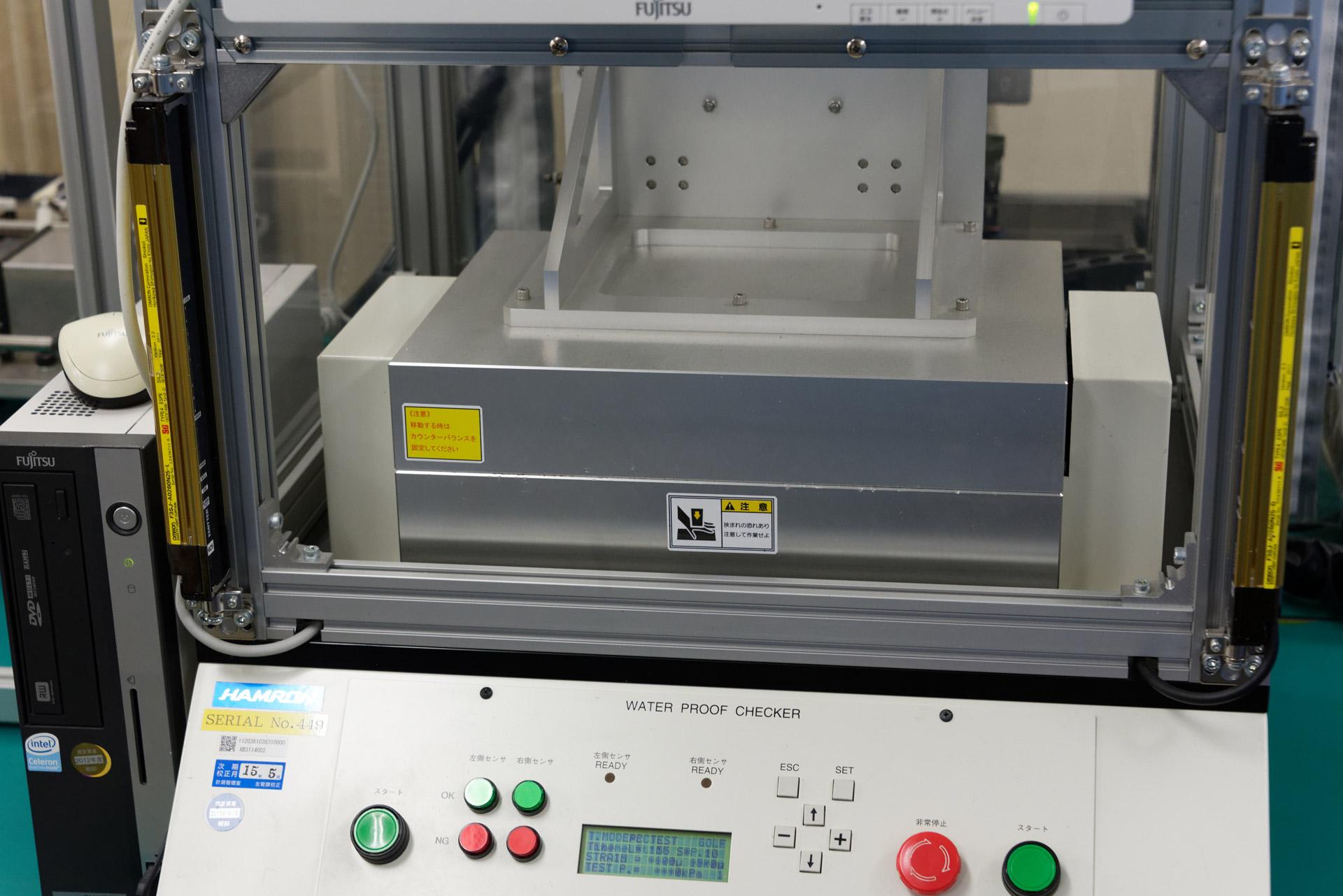 エアリーク試験。端末に空気圧をかけることで、一定以上の気密性が保たれている場合は端末自体が変形する。その変形量を計測することで、防水性能を正しく有しているかを確認する