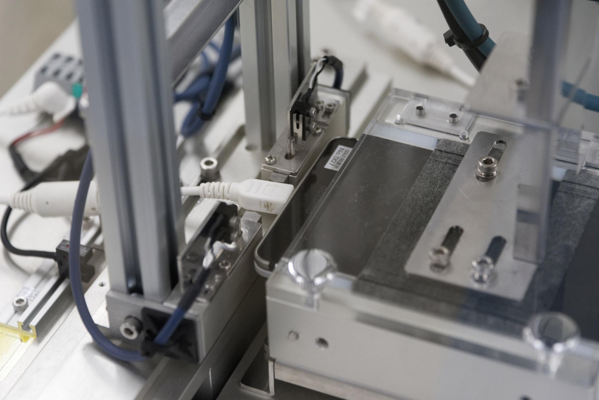 コネクタ耐久試験。USBケーブルを接続した状態で、コネクタの根元に上下および左右方向から2kgの力を5000回ずつ加え、問題ないことを確認する