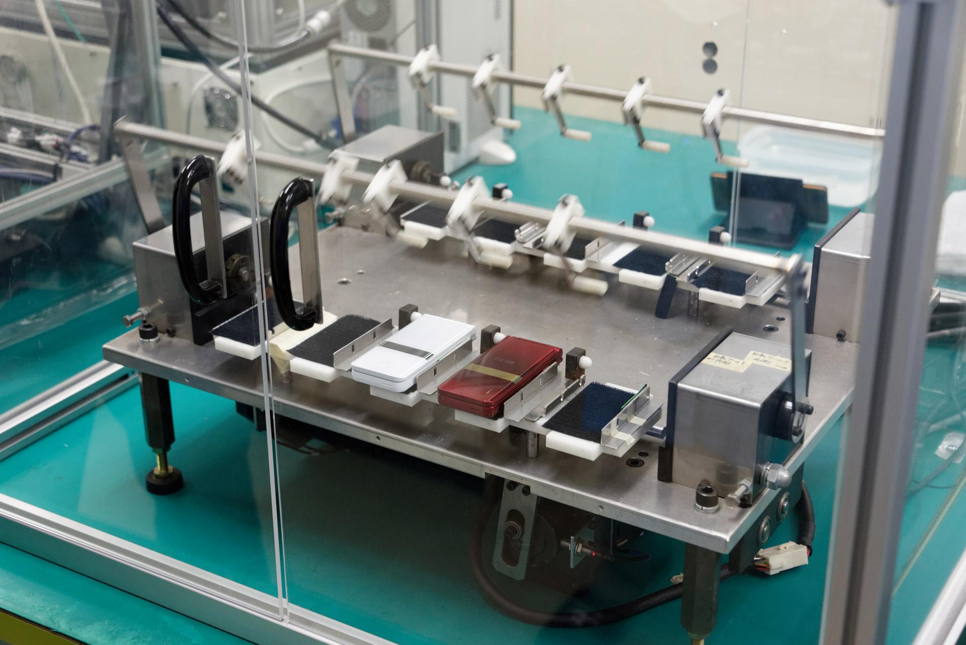 折りたたみ型携帯電話の開閉を11万回繰り返す、ヒンジの耐久試験を行う機材もある
