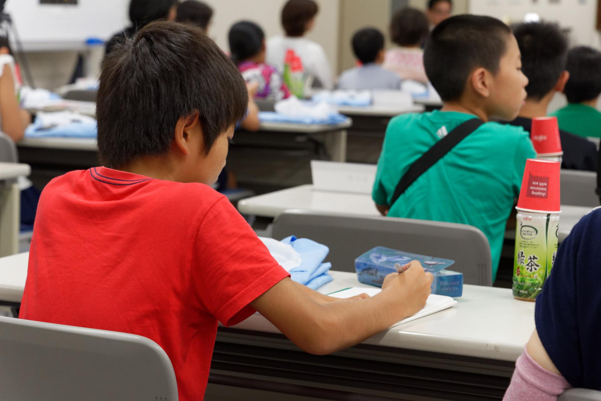 工場の社員に積極的に質問する子供や、説明を聞いて熱心にメモを取る子供の姿も