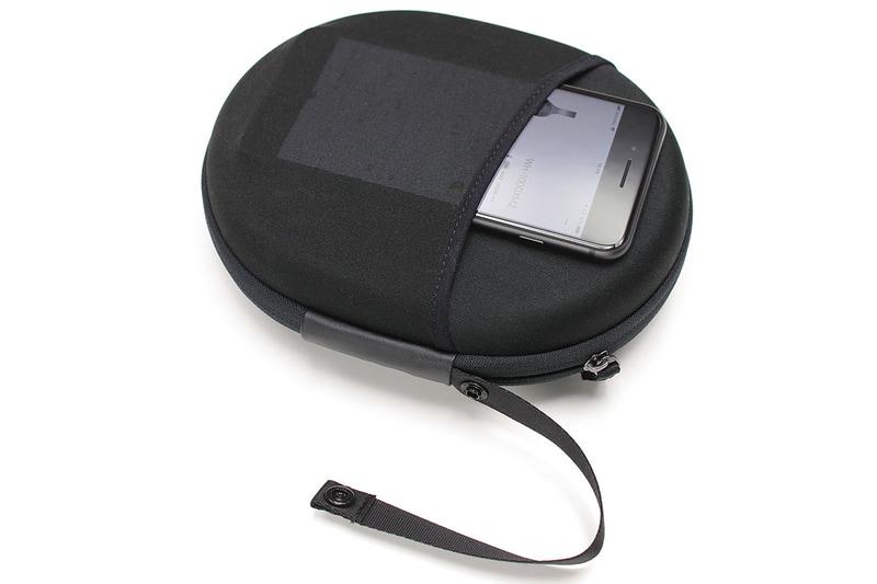 ケースの厚みは約50mm。外寸200×160mmの楕円で、意外にコンパクトに携行できます。ケース裏面には伸縮性のあるポケットが付いていて、ポータブルオーディオプレイヤーなどを入れることもできます。スナップボタンでループを開閉できるストラップが付いていて、バッグやバックパックの定位置からズレないように固定できたりしてナニゲに便利。