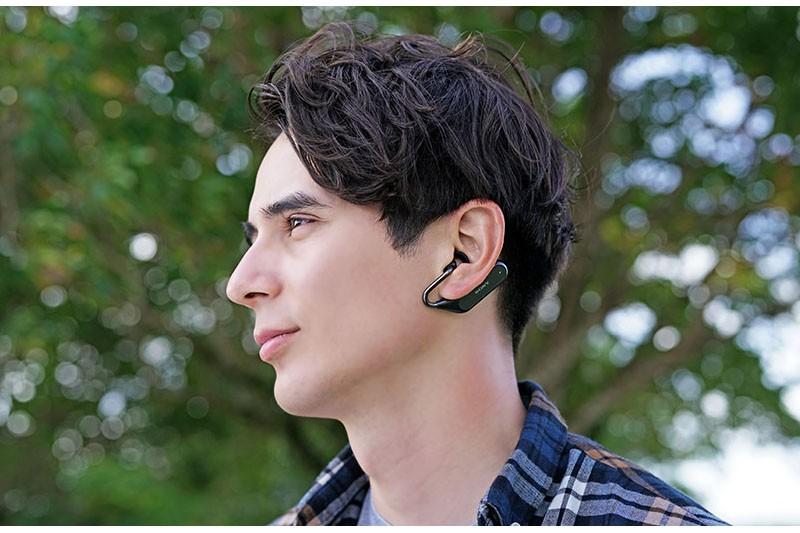 左写真のように、耳の下側に掛けて使います。重量が分散されるため、自然な装着感があり、やや激しく動いても耳から落ちにくいフィット性があります。通常使用に加え、「音声による情報を受けるヘッドセット」として常時装着ができるほか、IPX2の防滴仕様なのでスポーツやアウトドアアクティビティにも向きます。
