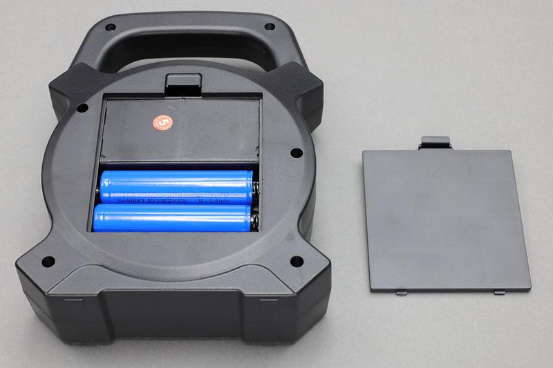 """LightsEtcのLED小型投光器(<a href=""""http://amzn.asia/gCWeull"""" class=""""strong bn"""" target=""""_blank"""">Amazon.co.jpへのリンク</a>)。18650×2本付きで税込1550円! 電池はもちろん脱着可能で、本体にセットした18650へはUSB充電が可能です。USB給電機能もあり、スマートフォンなどをUSB充電可能。LEDライトは、前面中央、前面周囲、前面上部の3つがあり、中央と周囲は白色投光で、上部は赤や青の点滅。白色投光は2畳程度の広さを十分明るく照らし出せる光量が感じられます。ただし、つくりは値段なりという雰囲気。"""