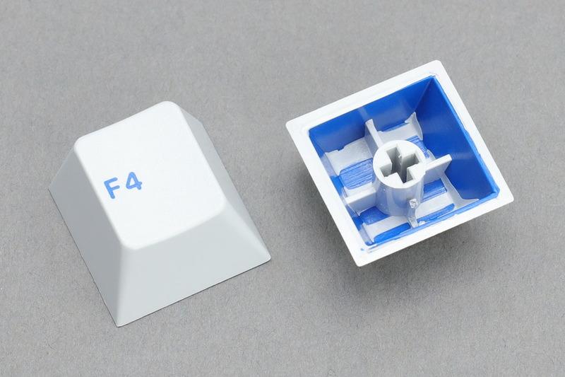 ダブルショットキーキャップの一例。それぞれ2色の樹脂を使ってつくられています。白+青、グレー+青ですが、これらキーキャップの場合は青がキートップ刻印となり、白やグレーがキーキャップ全体の色になっています。