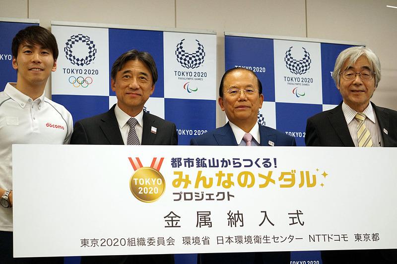 納入式の様子。左からリオパラリンピック銅メダリストの山田選手、NTTドコモの吉澤社長、武藤東京2020組織委員会事務総長、藤吉秀昭日本環境衛生センター副理事長