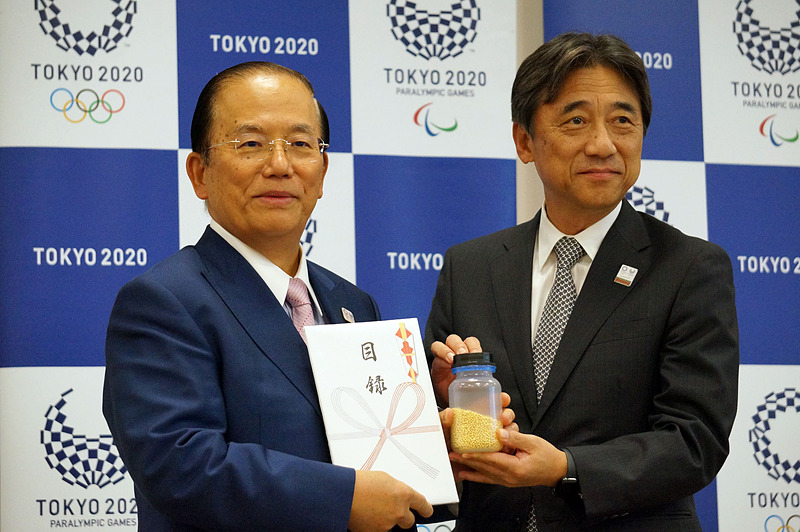 納入されたリサイクル金属の目録を手にする武藤事務局長(左)と、ドコモの吉澤社長(右)