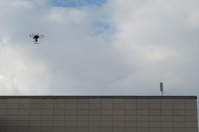 飛行するドローンと屋上に設置された5Gのアンテナ
