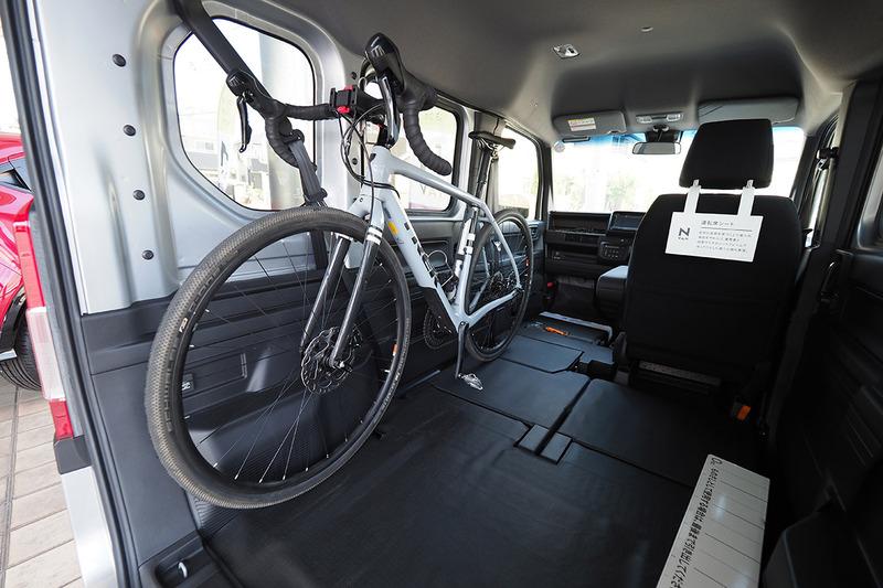 助手席を倒せば、後部とつながった状態のフルフラットになります。車体左側が大開口で、助手席~後部がフルフラットになりますので、自転車を左側からポンと載せられちゃう! 右写真は自転車を逆向きに載せて後部から見た様子。ロードバイクなら2台並べて載せられ、後部右側の座席に座ることもできます。