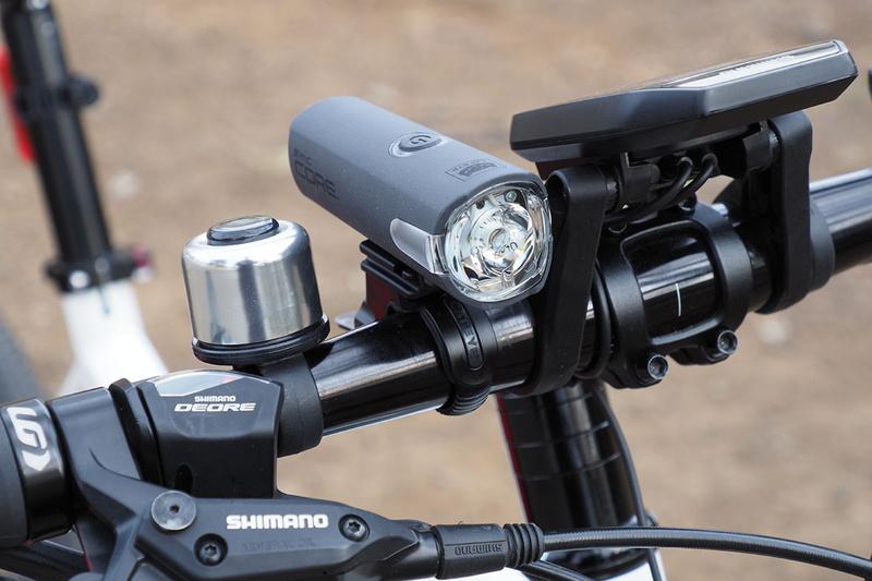 """ヘッドライトの「SYNC CORE」(<a href=""""https://www.cateye.com/jp/products/headlights/HL-NW100RC/"""" class=""""strong bn"""" target=""""_blank"""">公式ページ</a>)が点灯する様子。左は消灯で、右は点灯。曇天下での点灯イメージです。どのモードで光らせても、直視するのが危険もしくは目に強い残像が残る程度、明るいライトです。"""